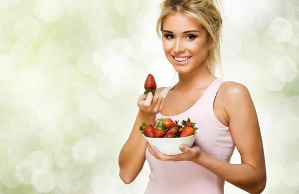 Beautiful smiling woman with red strawberry