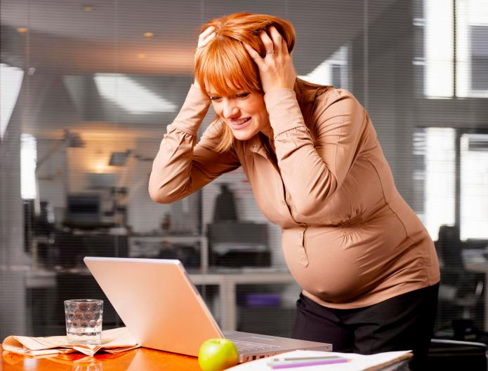 Pregnant woman in office, looking at