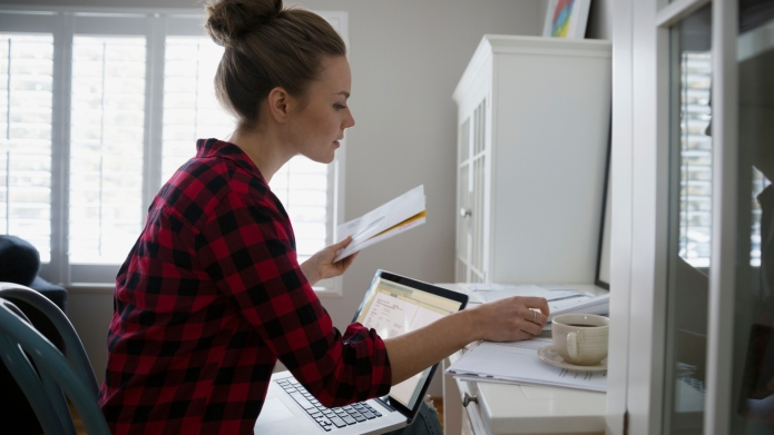 Woman with laptop paying bills online