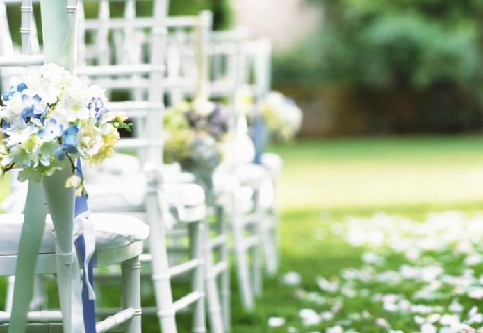 Rows of chairs beside grassy aisle