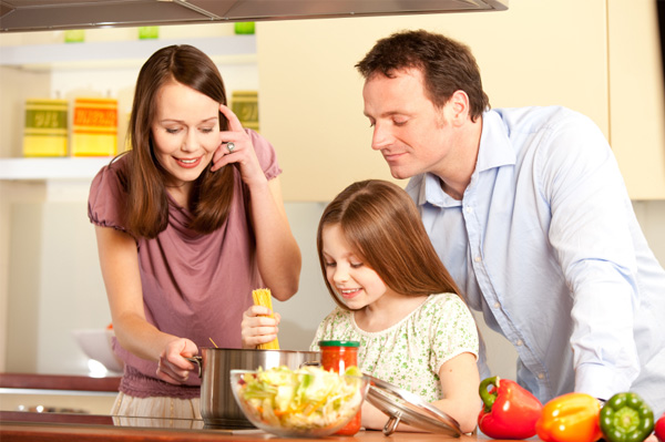 family cooking pasta
