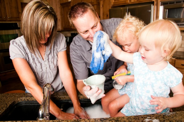 family washing dishes together in modern kitchen