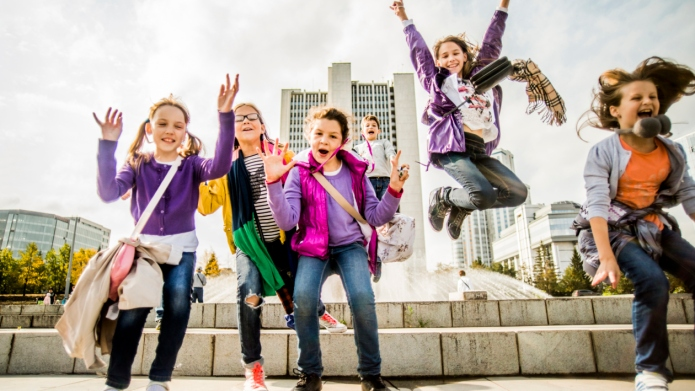 Caucasian children cheering in city square