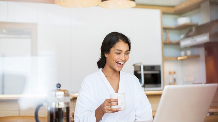 Laughing woman in bathrobe drinking coffee