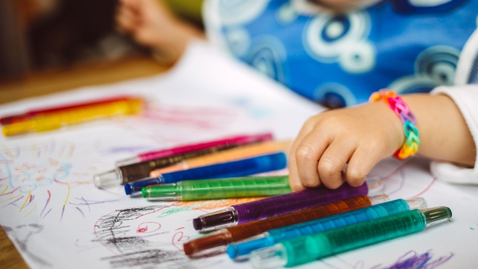 Little girl drawing with crayons in