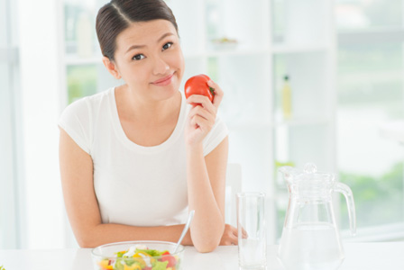 Girl in modern kitchen eating healthy lunch