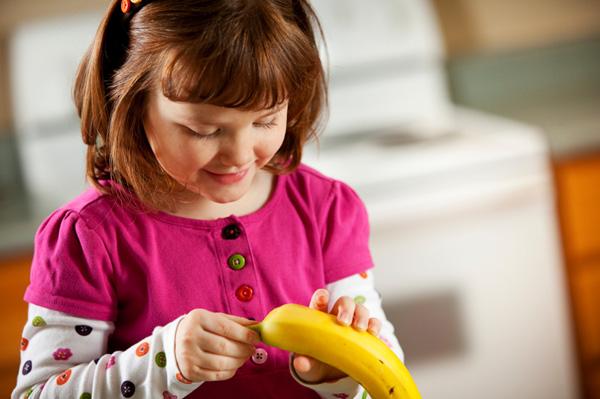 Girl peeling banana