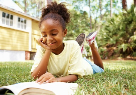 Girl reading classic book outdoors