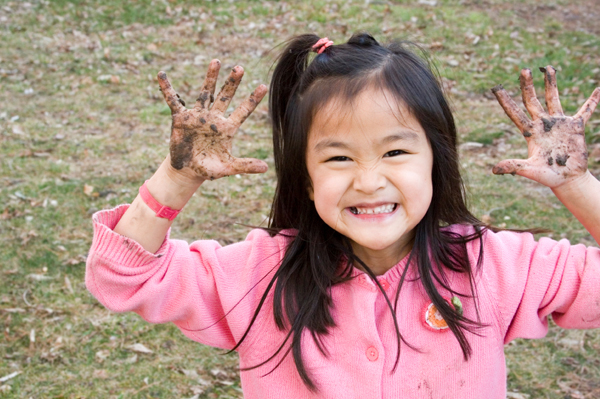 Girl with muddy hands