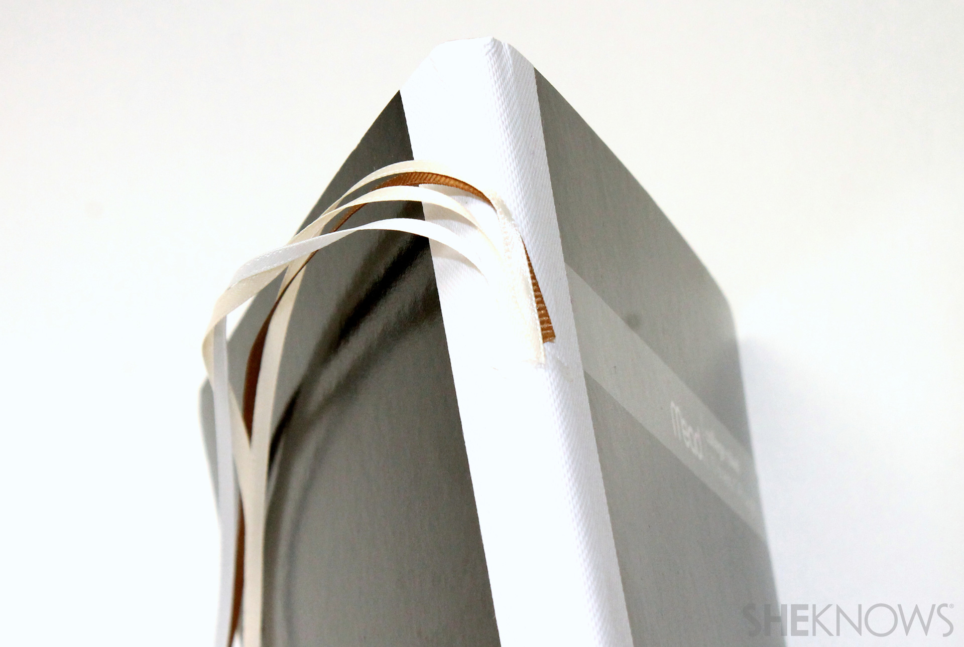 fabric covered composition book: Glue one end of the satin ribbons to the spine