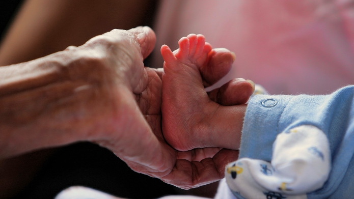 Baby feet and hands of elderly.