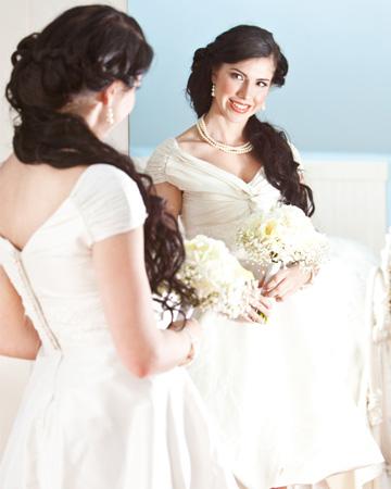 Happy bride looking in mirror