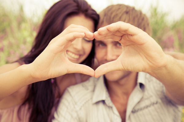 Happy couple with hands in heart formation