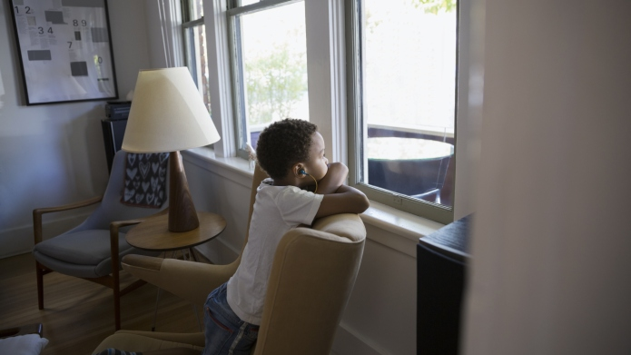 Boy with headphones looking out living