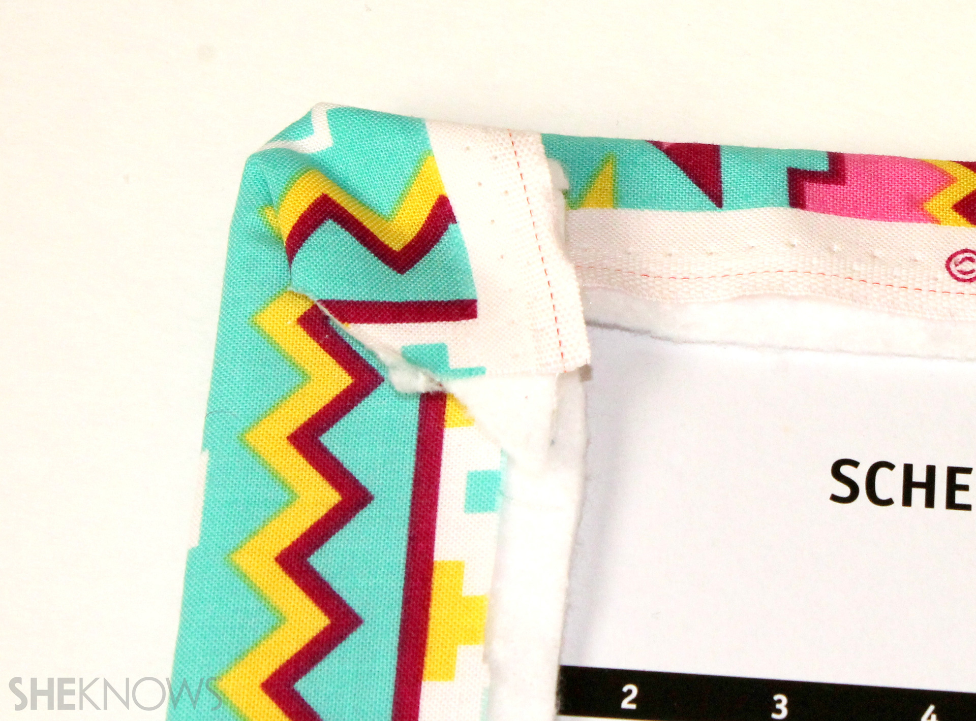 fabric covered composition book: For the corners, trim excess fabric and then fold and glue