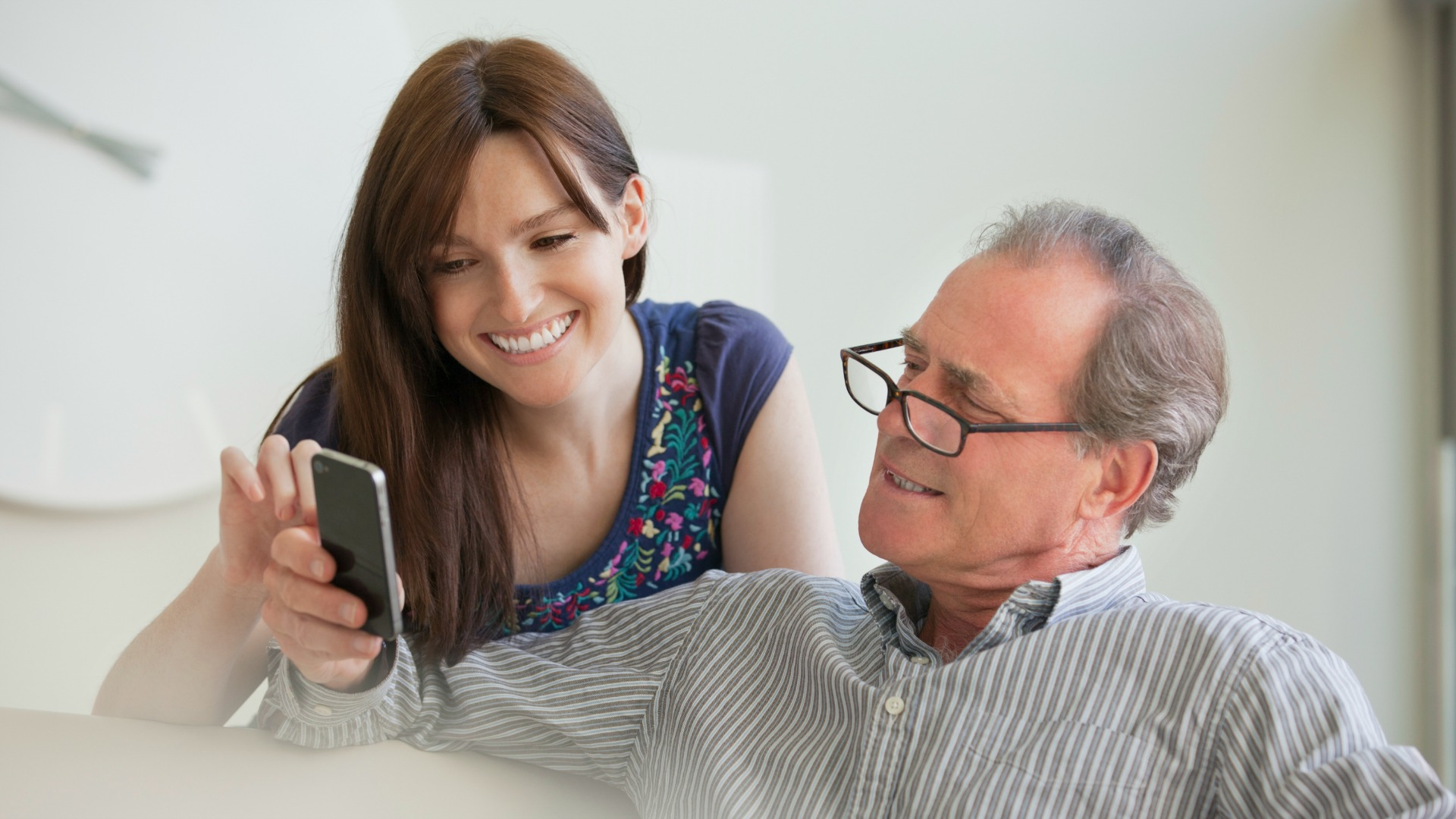 father and daughter look at smartphone together