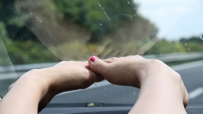 Feet resting on car dashboard