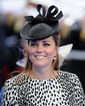 Kate wearing drop pendant earrings and black hat
