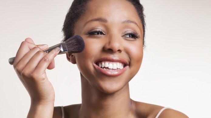 Lady laughing while applying blush brush