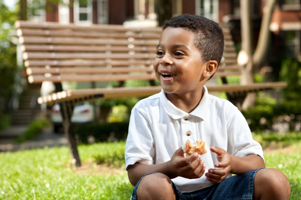 Little boy eating sandwich on the go