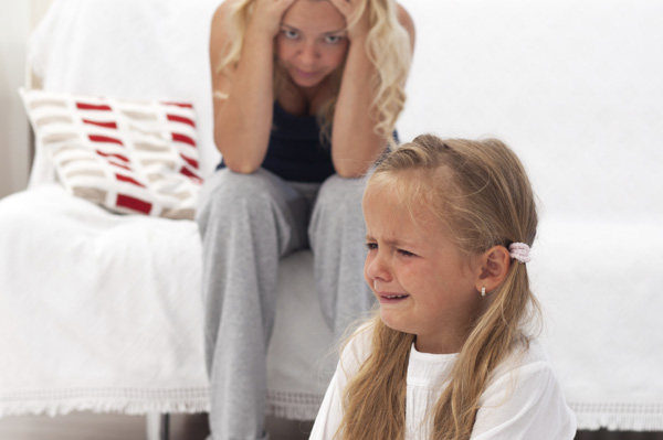 Little girl having tantrum in front of frustrated mother