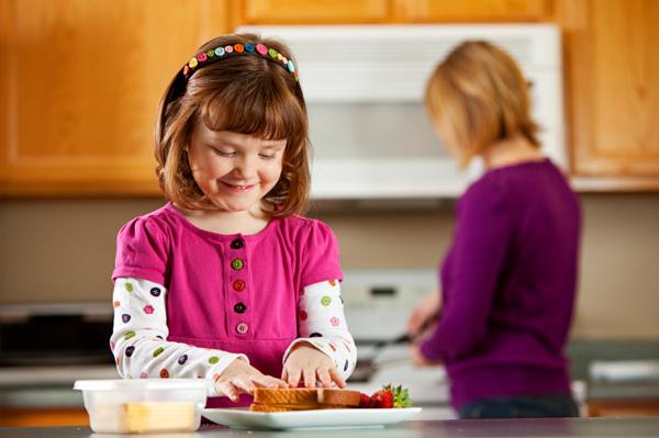 Little girl making sandwich