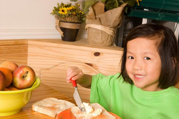 Little girl making toast