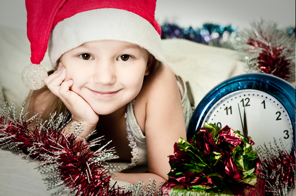 Little girl with clock on New Year's Eve