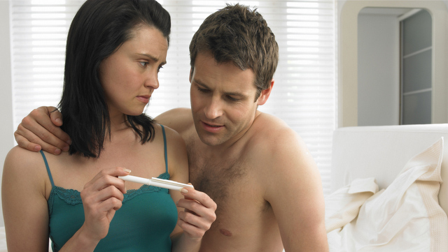 Couple in bedroom, looking at pregnancy