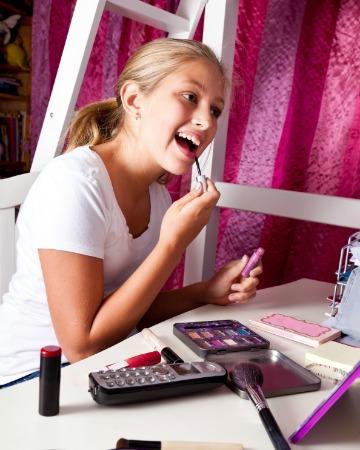 Tween girl applying makeup