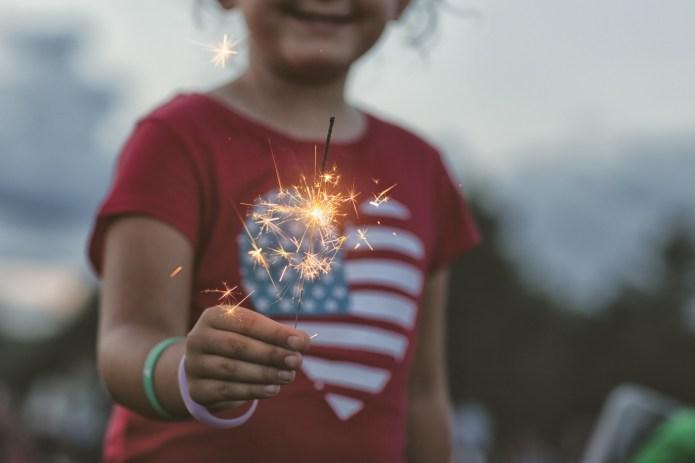 midsection of girl holding lit sparkler