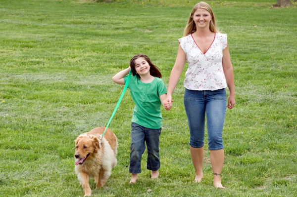 Mom walking dog with daughter