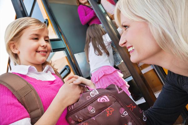 Mom handing daughter lunchbox