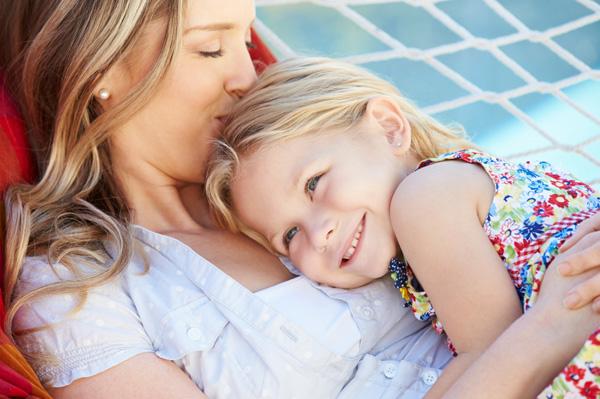 Mom holding daughter on hammack