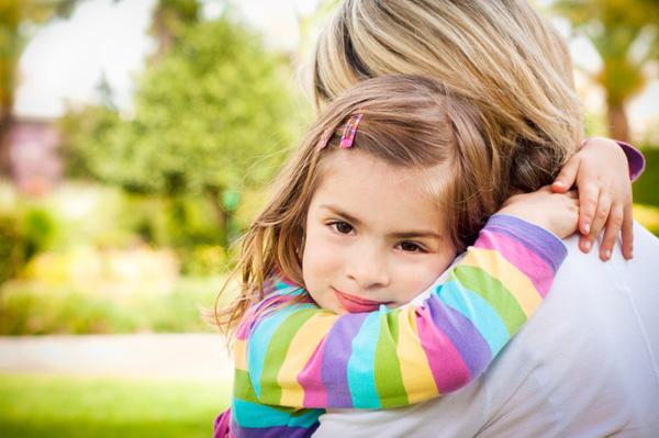 Mom hugging little girl