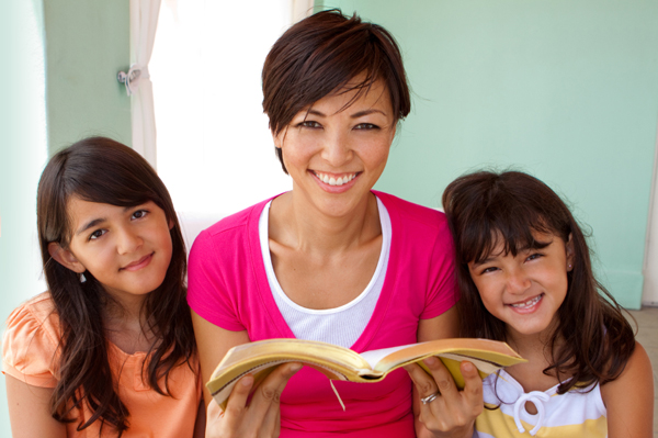 Mother and two children happily reading a book