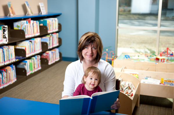 Mom reading to toddler at library