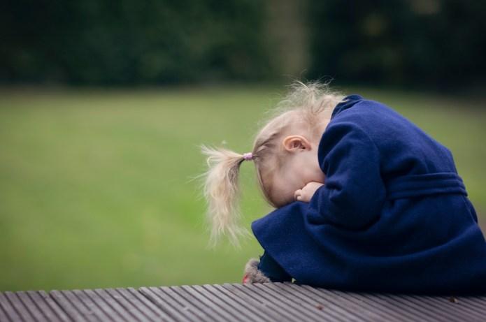 Little girl hiding her face in