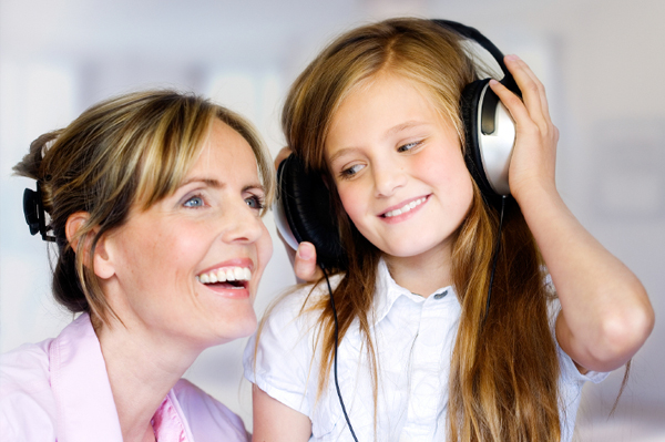 Mom and tween daughter listening to music
