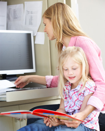 Mom working from home with daughter nearby