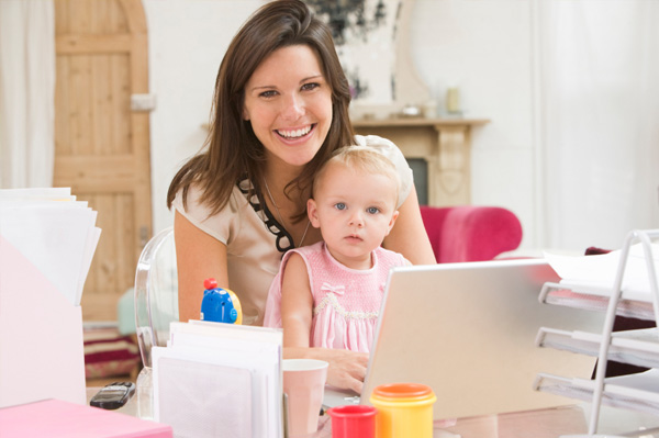 mom working on laptop with child on lap