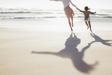 Mother and child running on beach | Sheknows.com