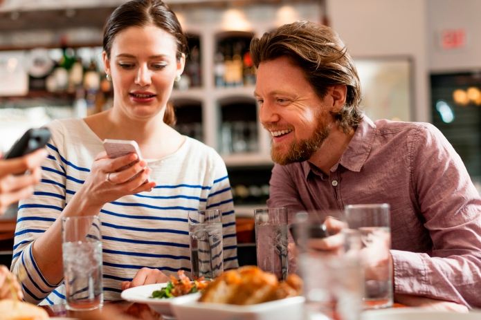 Friends at restaurant texting and showing