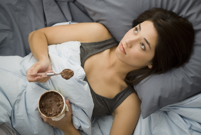 Woman lying down in bed spilling