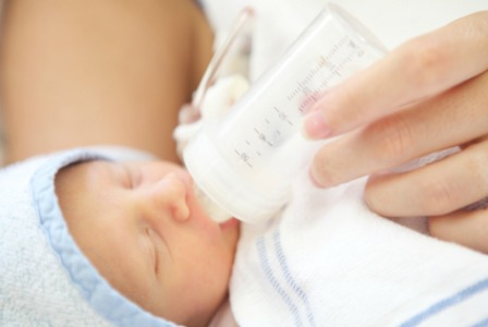 Newborn baby drinking bottle