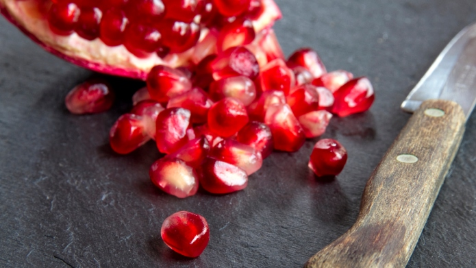 Pomegranate and knife on a piece