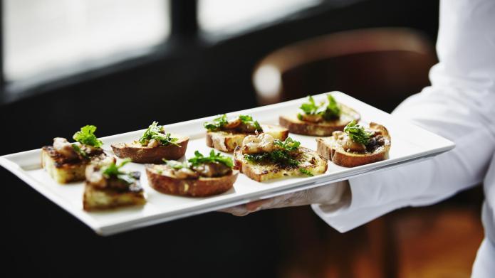 Waitress holding platter of organic appetizers
