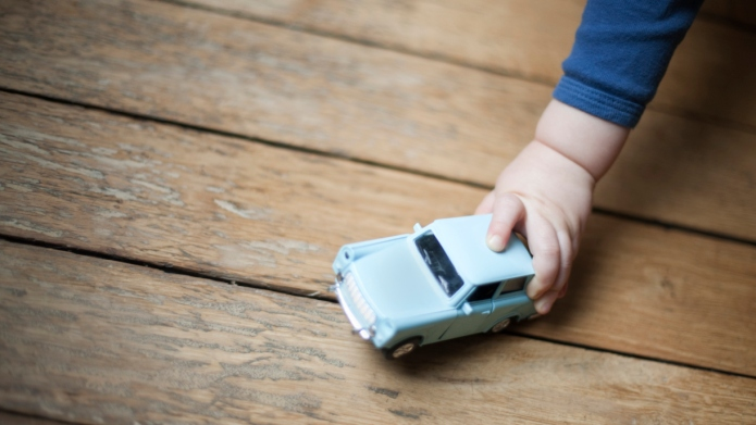 Child's hand holding toy car