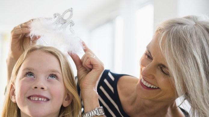 Senior Caucasian woman crowning granddaughter