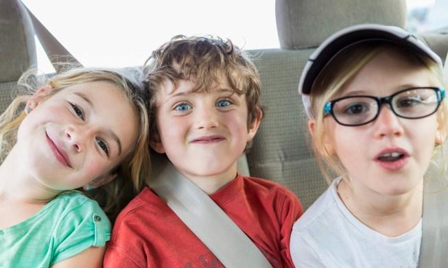 Caucasian children smiling in back seat